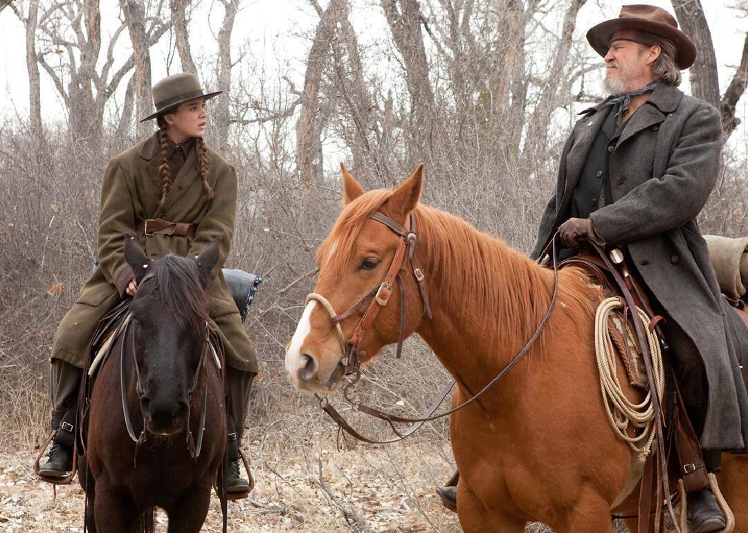 A imagem mostra uma garotinha em cima de um cavalo. Ela olha para um homem que também está em cima de um cavalo. Ele usa tapa-olho e chapéu. Eles estão em uma floresta seca.
