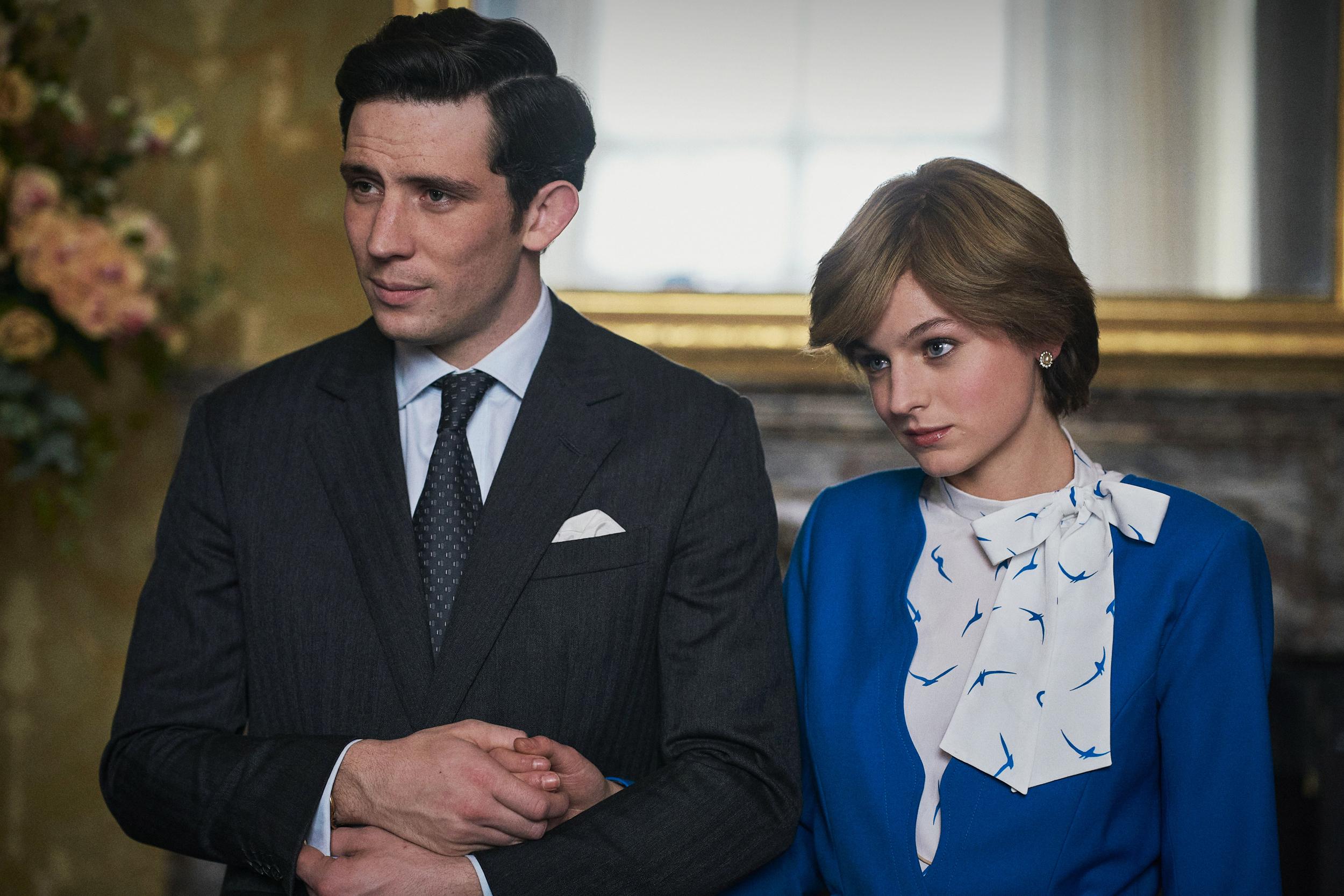 Na foto, Príncipe Charles, moreno e alto, veste um terno cinza escuro. Enquanto, Diana veste um vestido azul com um lenço branco estampado.