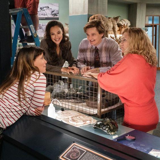 A imagem mostra, da esquerda para a direita, Patty Jenkins, Gal Gadot, Pedro Pascal e Kristen Wiig no set de filmagens do filme. Eles estão em torno de peças arqueológicas.