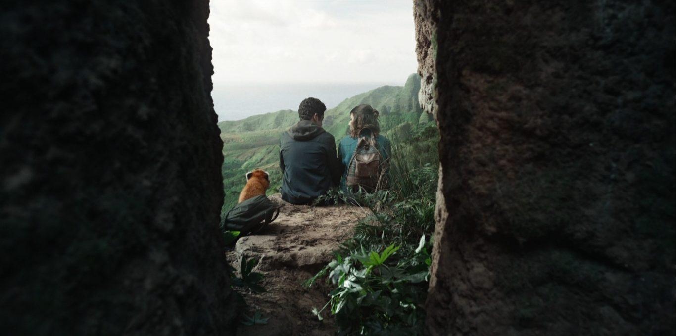 Pan, em forma de panda vermelha, Will e Lyra estão sentados na beirada de um penhasco. Ao fundo, pode-se ver uma floresta. A câmera se posiciona atrás deles, mostrando as costas.