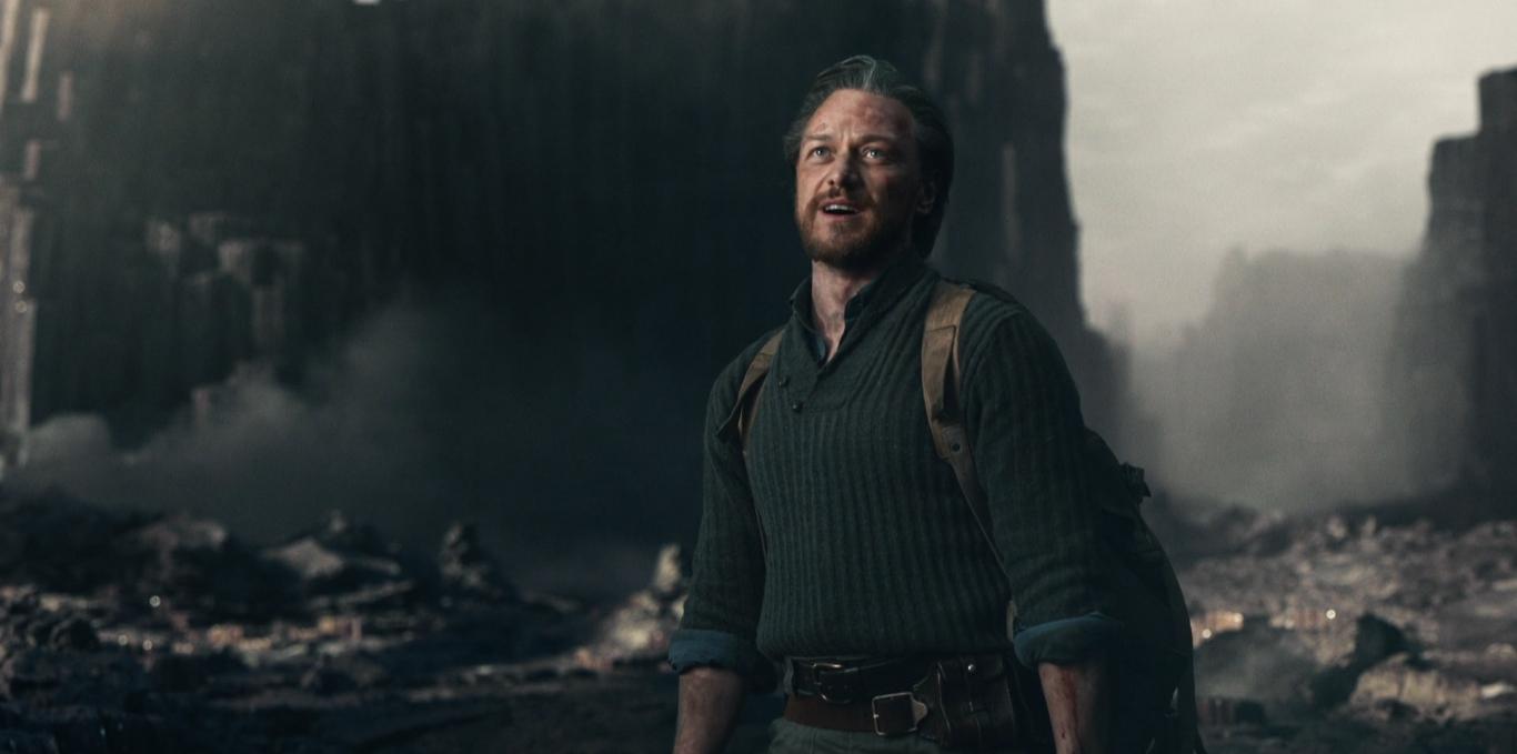 A foto mostra Lorde Asriel em primeiro plano, olhando para cima. A câmera filma de frente. Ele está sujo e veste um suéter e uma mochila. Ao fundo, vemos grandes paredões de pedra e um céu cinza.