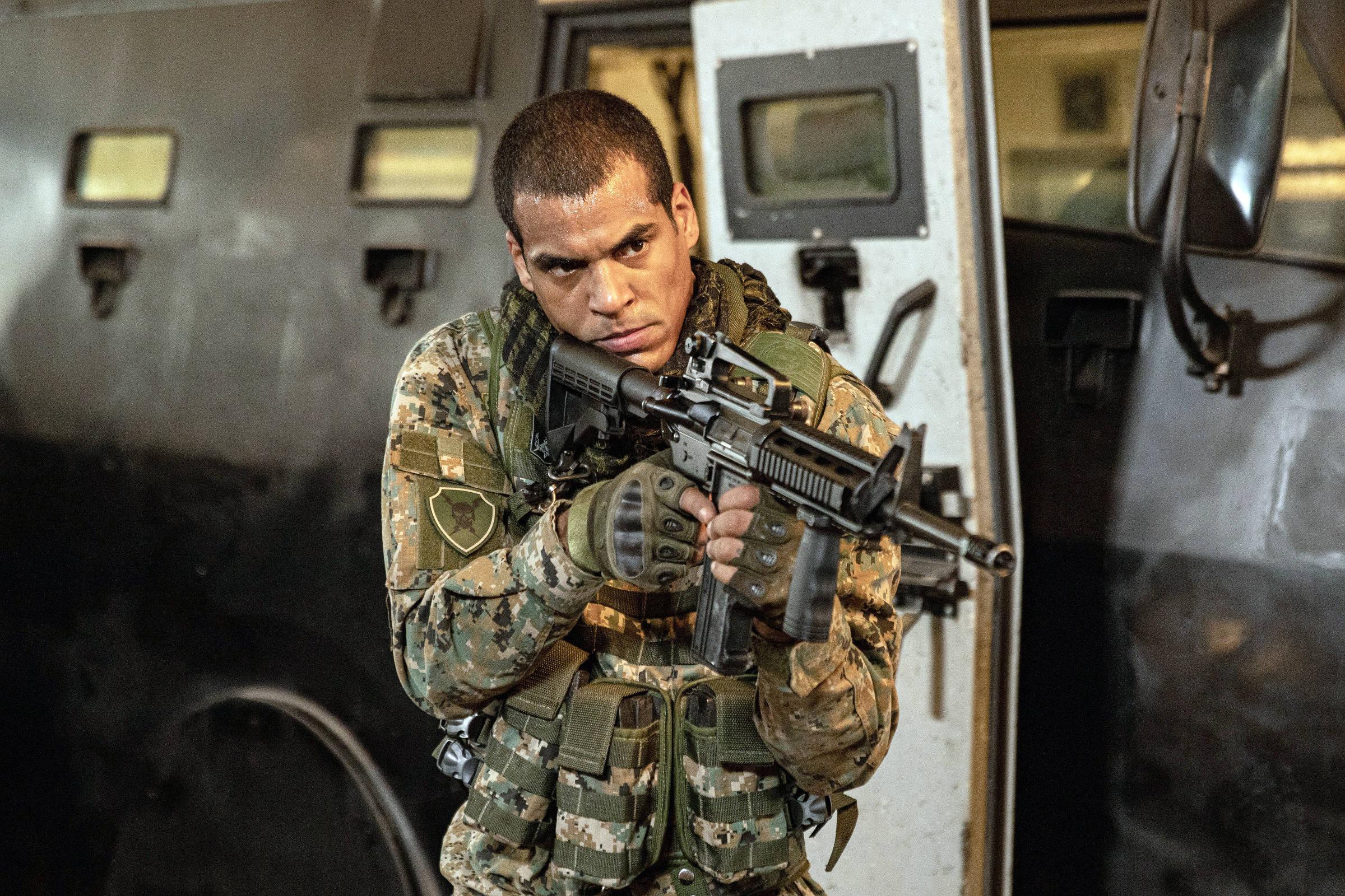 Cena da série Arcanjo Renegado. A imagem mostra o personagem Mikhael, interpretado pelo ator Marcelo Mello Jr., na frente de um carro forte arma e vestido com um uniforme do excército. O personagem tem a pele negra clara, cabelos raspados e olha com uma expressão séria e concentrada para fora da imagem, mirando a arma.