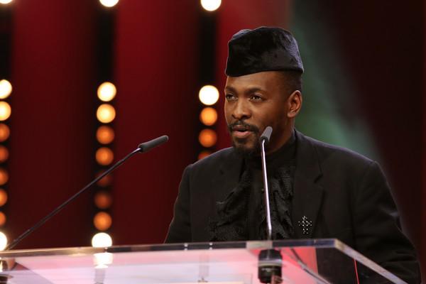 Lemohang, um homem negro de 40 anos, discursa em um palanque com dois microfones próximos ao rosto e podemos vê-lo apenas do peito para cima. Ele usa um paletó preto e um chapéu preto. Ele tem cabelos curtos, barba e bigode.