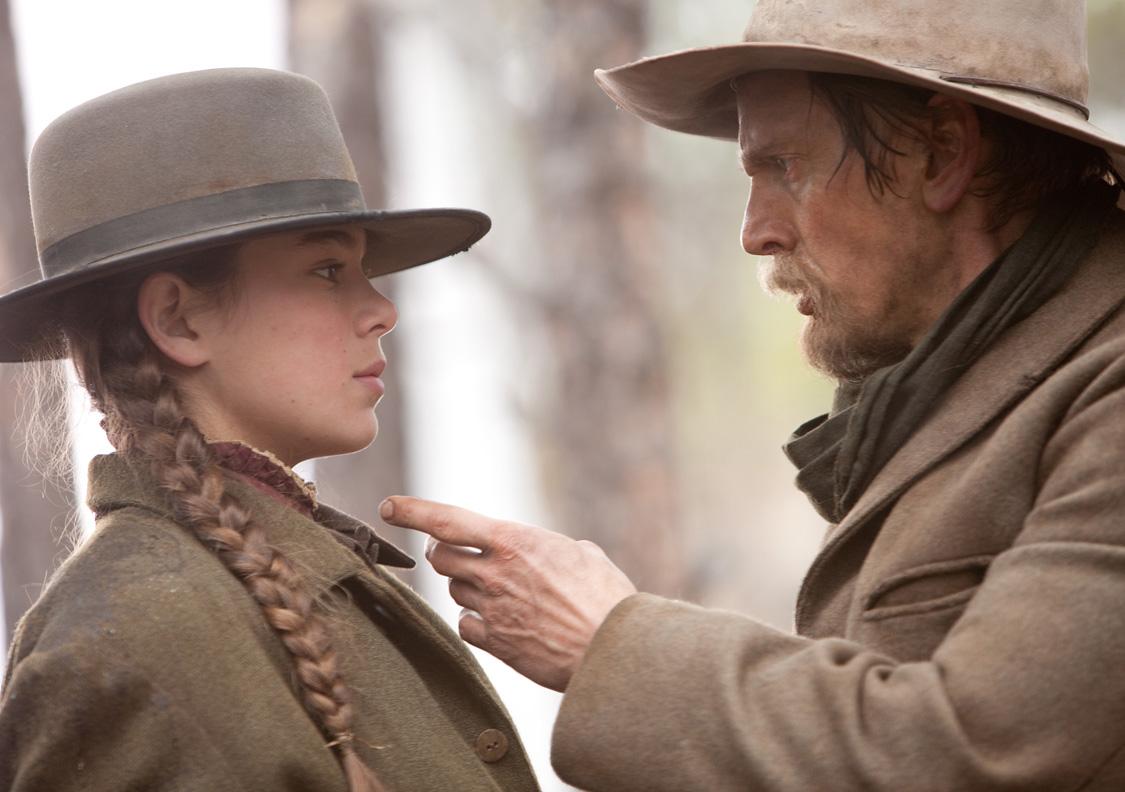 A imagem mostra um homem olhando para uma menina. Ambos estão de perfil. Ele aponta o dedo em direção ao rosto dela. Ela está com cara de assustada.