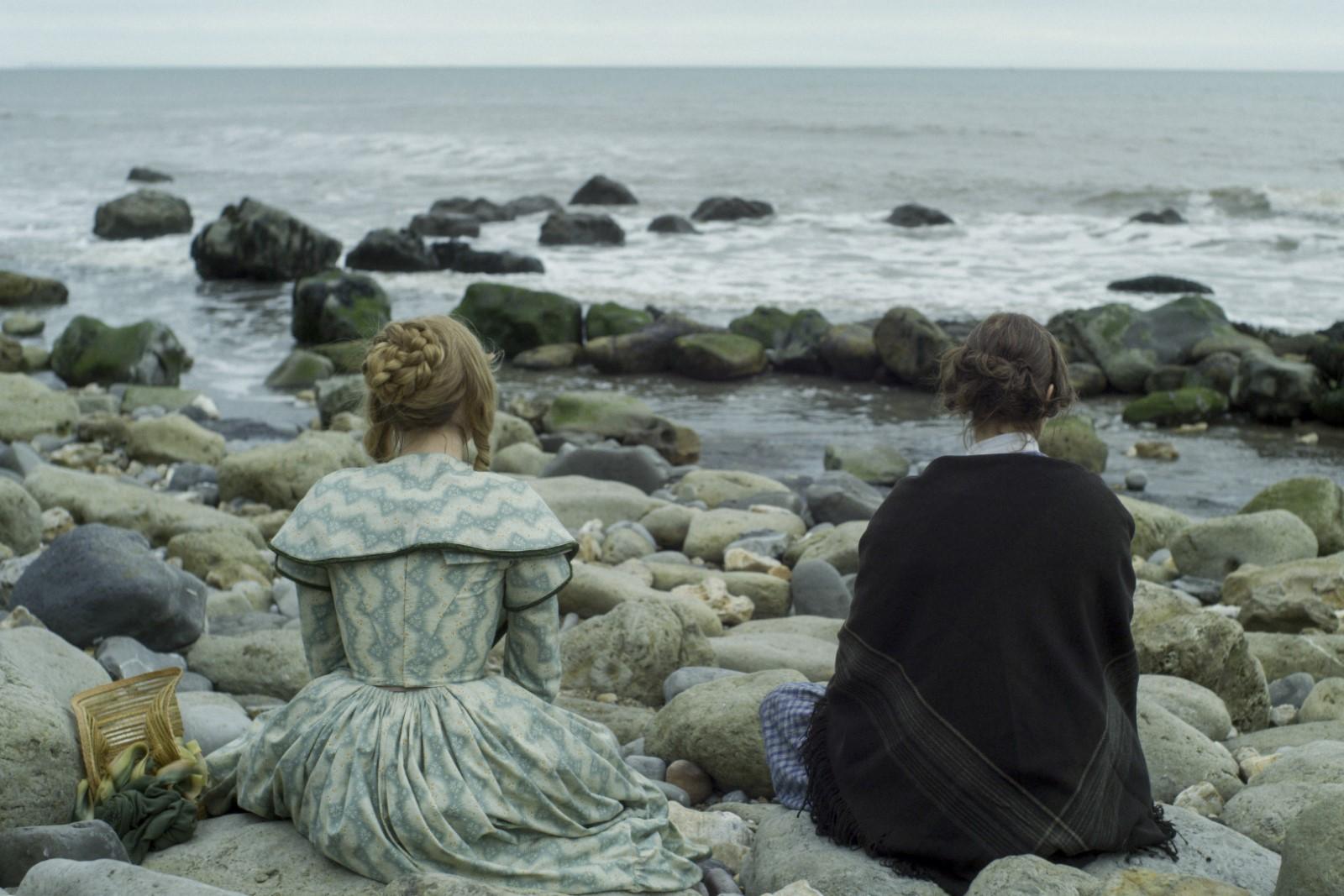 As duas mulheres estão sentadas nas pedras olhando para o mar. Saoirse, à esquerda, está usando um vestido azul claro e Kate, à direita, está de preto