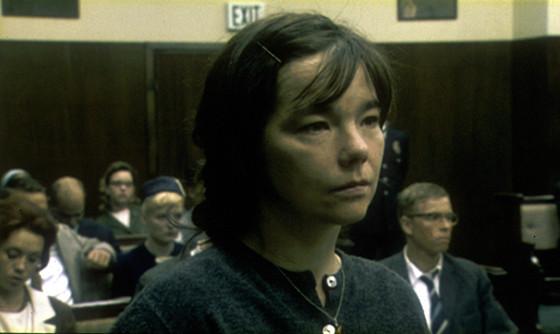 Cena do filme Dançando no Escuro. A imagem mostra Björk em um tribunal, olhando para a frente. O tribunal tem outras pessoas sentadas ao fundo.