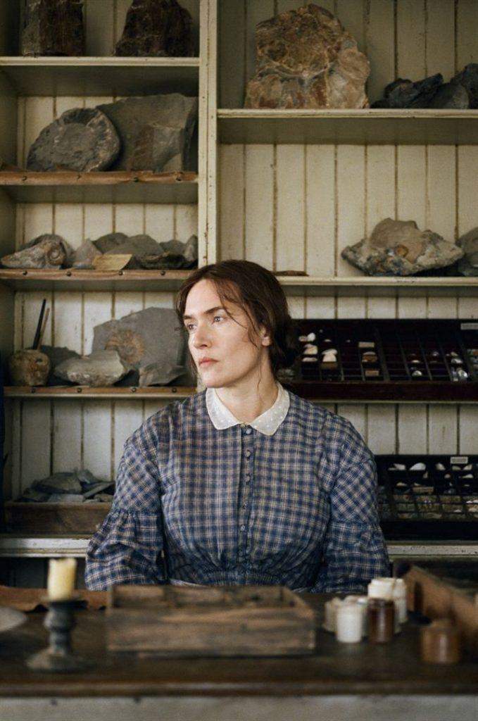 Kate Winslet está sentada à frente de um estante com pedras. Ela usa para a janela, está usando um vestido estampado em xadrez azul com gola branca