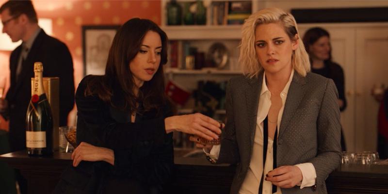 Na imagem, Riley e Abby juntas num bar. Riley possui cabelo castanho longo e veste um terno preto. Enquanto Abby veste uma camisa branca e blazer cinza, ela possui cabelo loiro descolorido.