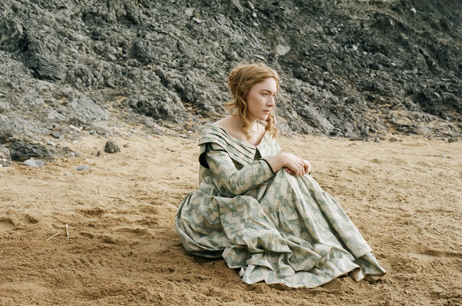 Saoirse está sentada sozinha na areia da praia. Ela tem os cabelos louros presos e usa um vestido com detalhes em verde. Atrás dela vemos uma grande rocha