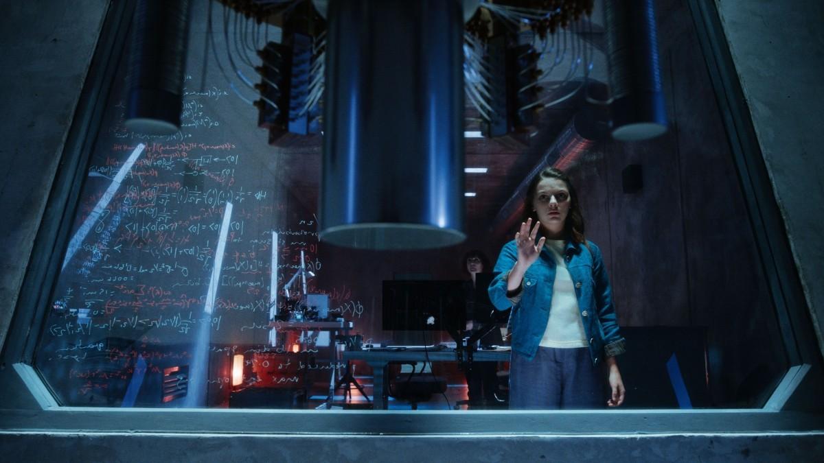 A imagem mostra um laboratório subterrâneo futurista. Em primeiro plano, há um cilindro de metal com um espaço vazio abaixo. Em direção ao fundo, Lyra está parada na frente de um vidro que a impede de acessar o cilindro. Ela apoia uma das mãos no vidro. Ao fundo, o resto dos equipamentos e a cientista Mary Malone, que observa a cena.