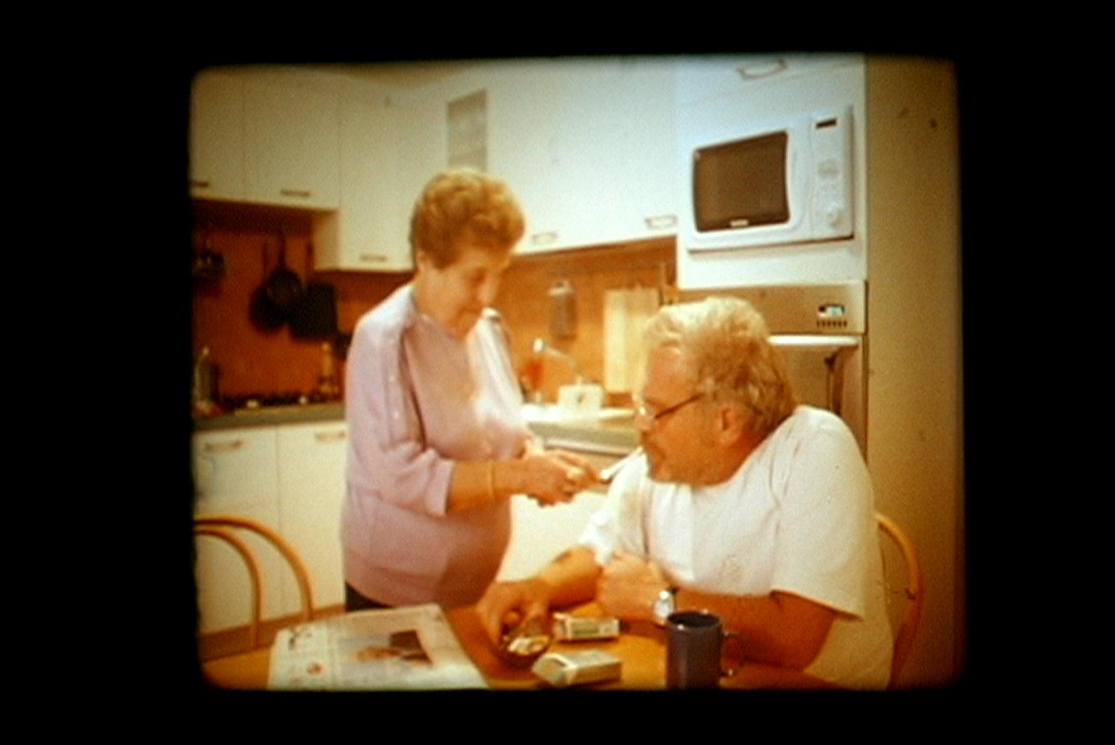 Cena de arquivo: imagem quadrada, tom sépia quente e um casal de idoso está na mesa da cozinha, ele usa camiseta preta e óculos, e tem cabelos brancos, ela veste camiseta clara e tem cabelo preto