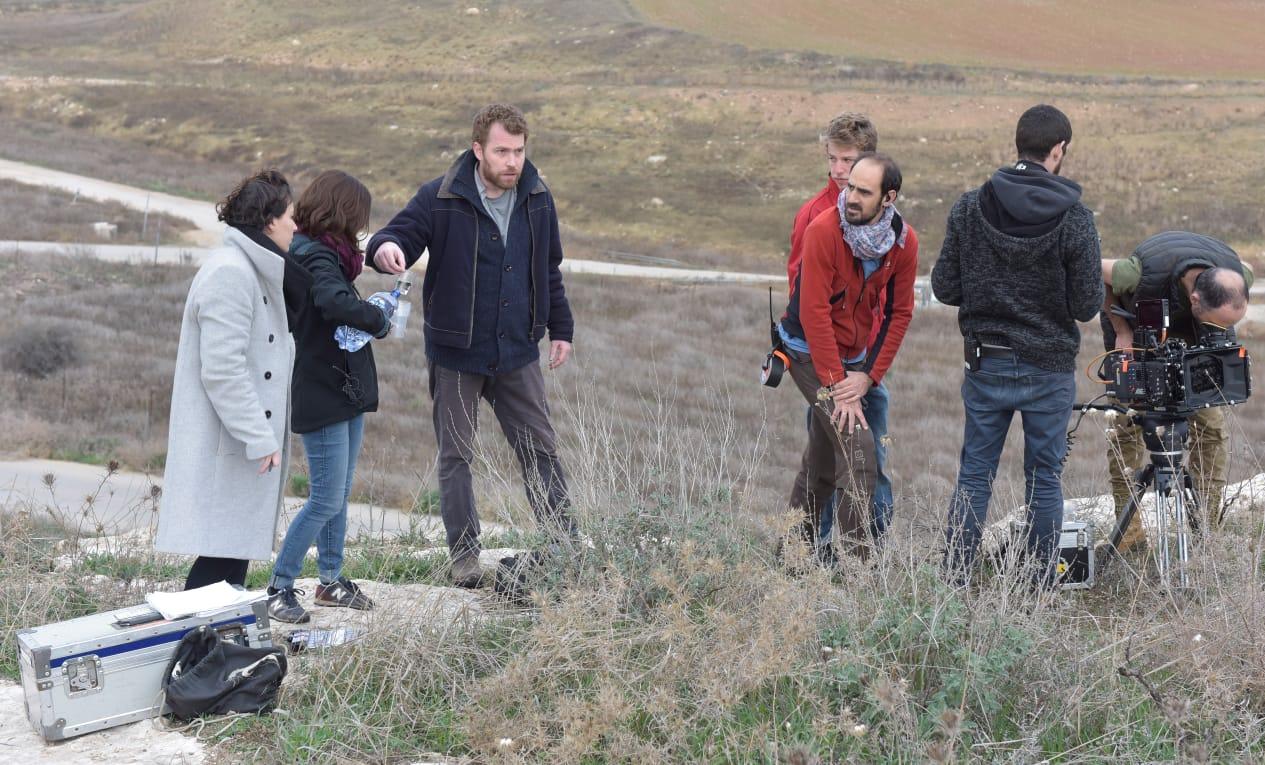 Cena dos bastidores do filme. 5 pessoas brancas estão reunidas, e no canto direito da foto está a câmera.