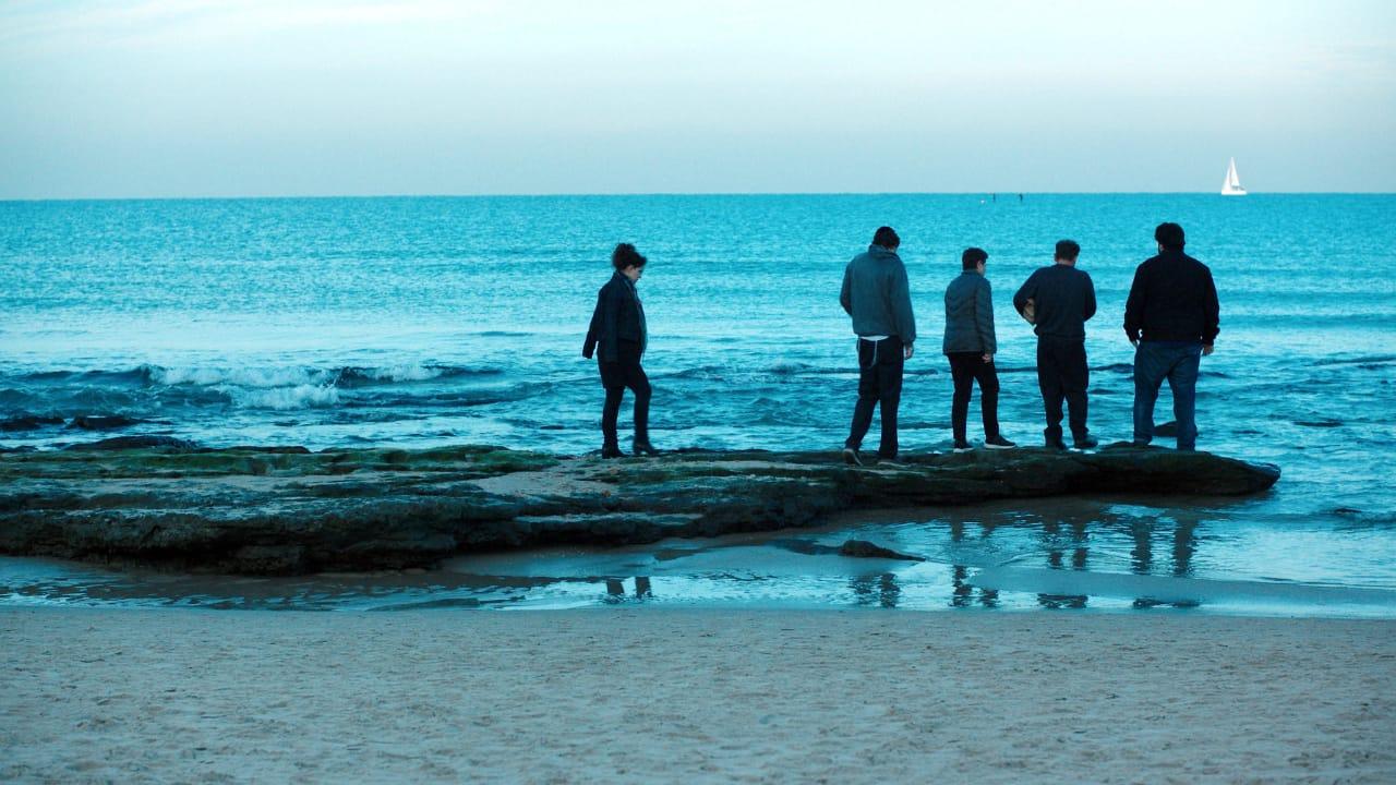 5 pessoas estão reunidas às margens do oceano, uma delas está mais afastada à esquerda, o mar é azul e o céu é azul mais claro
