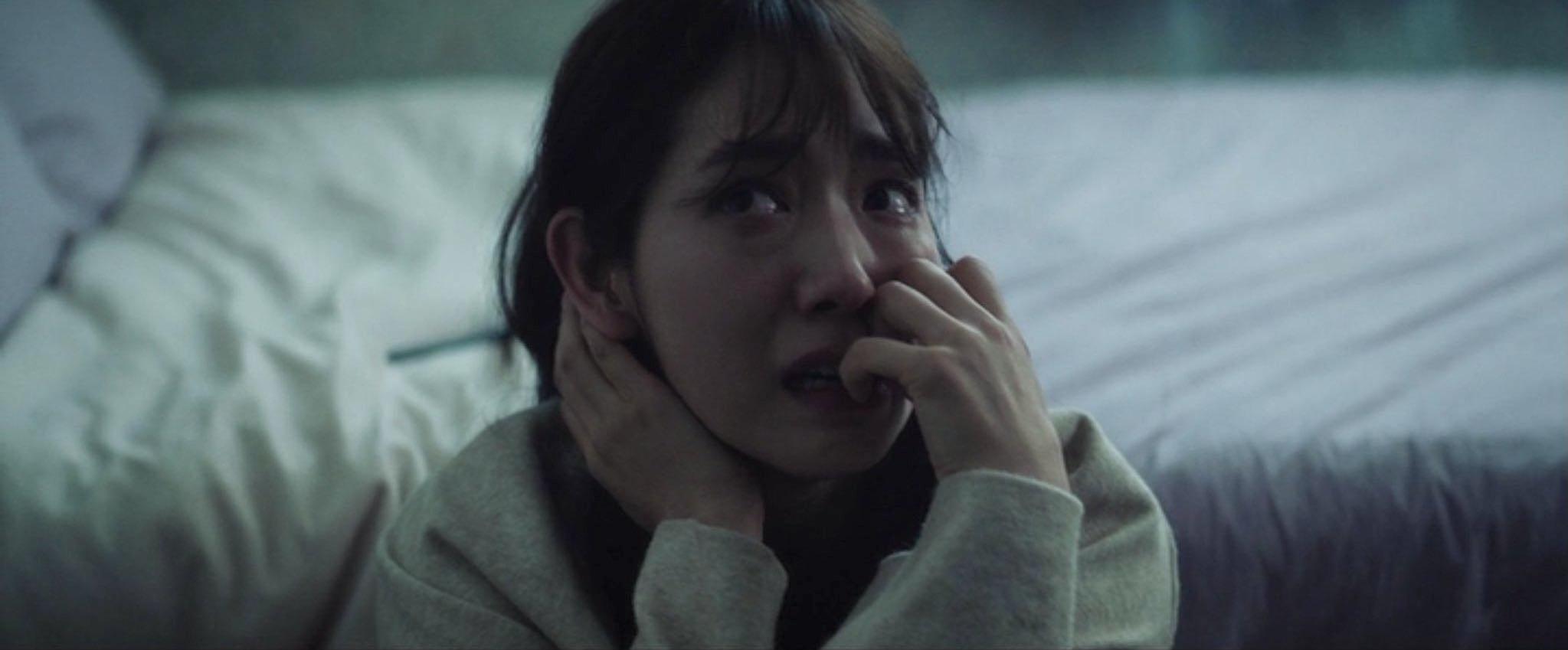 A imagem é de uma das cenas do filme. Nela, podemos ver a atriz Park Shin Hye sentada no chão, em frente à sua cama. Park é uma mulher de traços orientais, cabelos castanhos na altura dos ombros e franja. Ela veste uma blusa branca de mangas longas. Park está com uma feição assustada, com o olhar voltado para o canto superior esquerdo e roendo as unhas da mão esquerda.