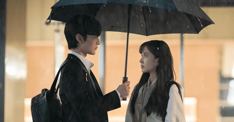 Cena da série Do You Like Brahms?, vemos dois adolescentes asiáticos, eles estão na chuva, amparados por um guarda-chuva, segurado pelo menino. Ele veste jaqueta preta e mochila da mesma cor, enquanto ela, de cabelos compridos, veste moletom bege. Eles se olham nos olhos.