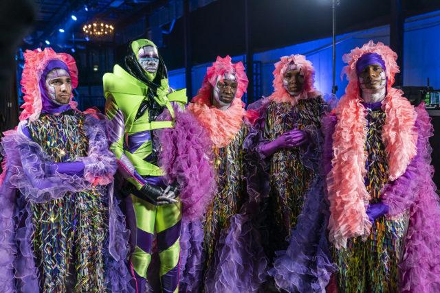 Cena do reality show Legendary. Vemos 5 indivíduos lado a lado, eles são negros e se vestem com tema espacial. São roupas coloridas e extravagantes, neon, com caudas, renda e maquiagem em verde, roxo e rosa