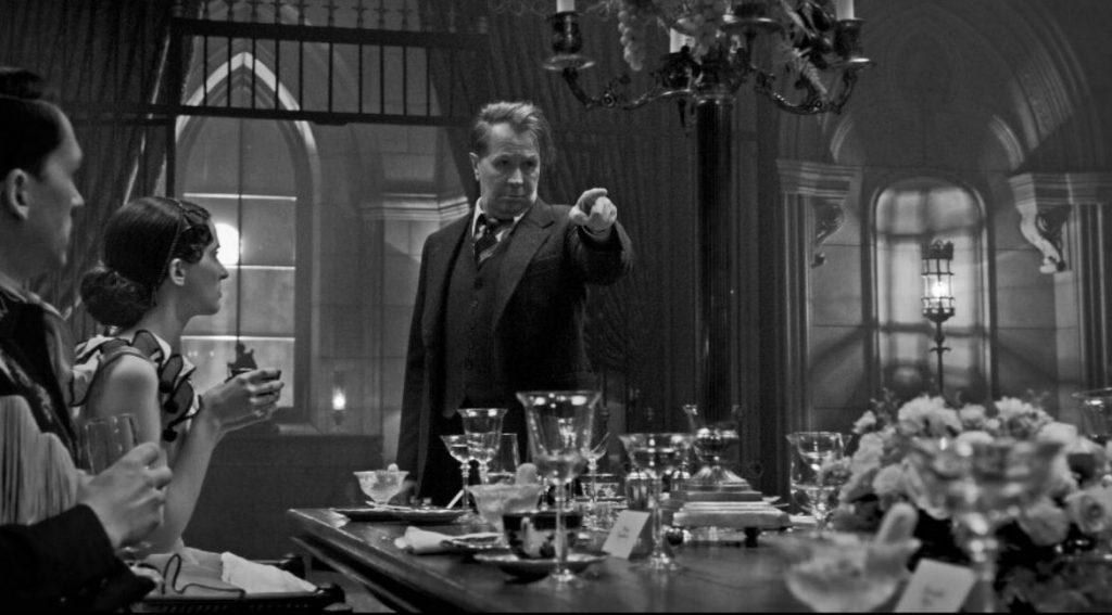 A foto está em preto e branco. Gary Oldman está em seu centro, usando um paletó e apontando o dedo esquerdo a frente. À esquerda, há duas pessoas o encarando. Ele está em frente a uma mesa, com diversos talheres, pratos e copos em cima. Acima dele, há um lustre.