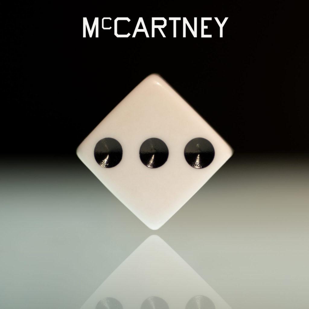 """Capa do álbum McCartney III. Um fundo preto com um dado ao centro e escrito """"McCartney"""" na parte superior."""