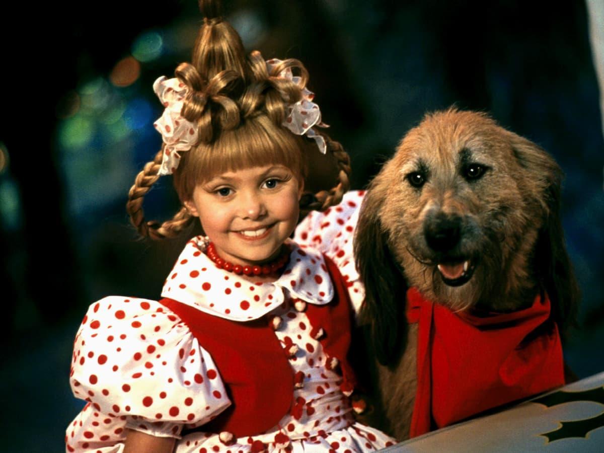 A imagem mostra a personagem Cindy Lou Quem ao lado do cachorro Max. Ela usa um vestido vermelho com mangas bufantes em branco com bolinhas vermelhas. Seu cabelo está preso para cima e é adornado com tranças. Max tem pelos castanhos claros e usa um cachecol vermelho.