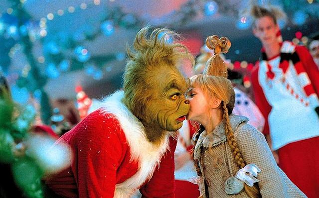 A imagem mostra o personagem Grinch vestido como um Papai-Noel, com um grande casaco vermelho. Ao seu lado Cindy Lou Quem veste um casaco bege e seu cabelo está preso em um coque alto com longas tranças soltas na lateral. Ela está beijando a bochecha de Grinch que parece surpreso.