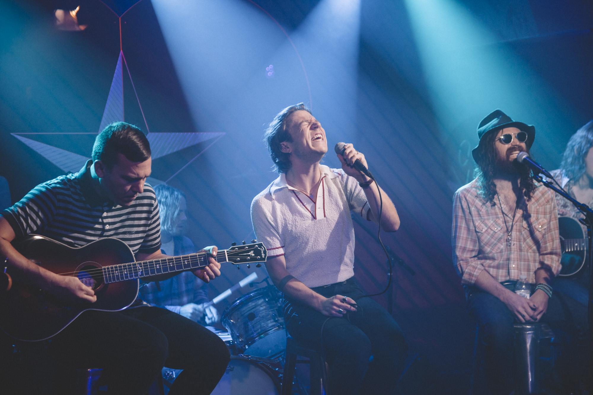 Foto de um show da banda, com Matt Shultz e Auerbach na frente do palco. Eles cantam usando microfones e estão sentados em bancos, perto deles está outro membro da banda