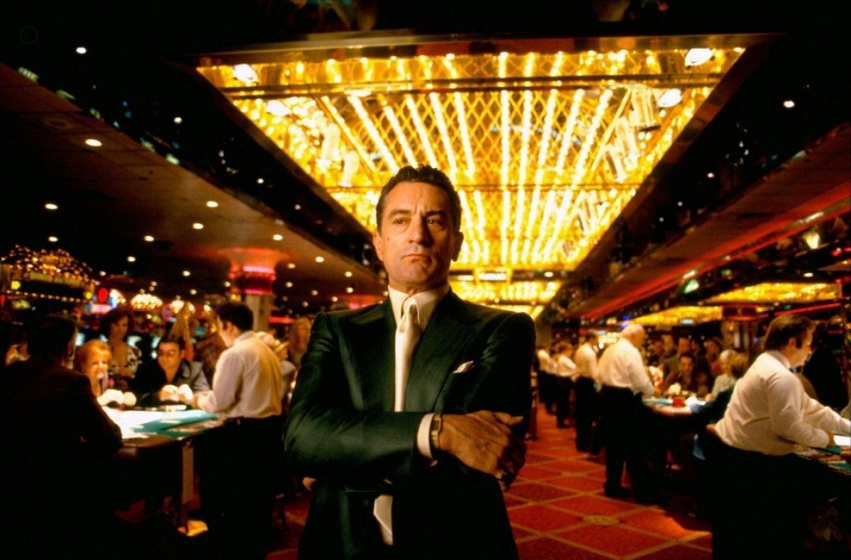 Cena do filme Cassino, que mostra o personagem de Robert de Niro, um branco de 45 anos, parado no meio de um cassino. Ele usa um terno preto com gravata branca e está de braços cruzados. Atrás dele, vemos luzes amarelas e um tapete vermelho, além de vários dealers, todos de camisa branca e calça preta