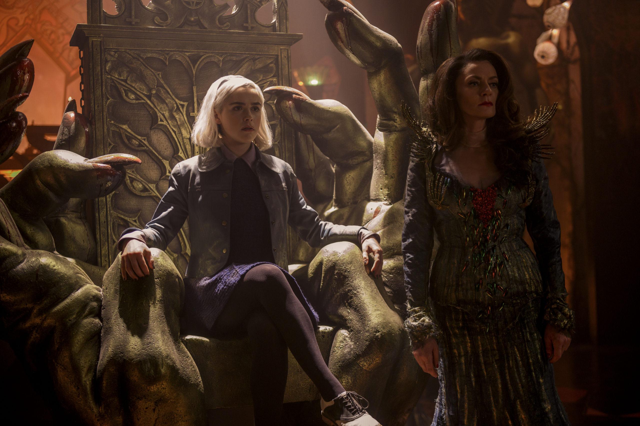 A imagem é de uma das cenas de O Mundo Sombrio de Sabrina. Nela, vemos a personagem Sabrina sentada em um trono, ao lado de Lilith, que está em pé. Sabrina é uma jovem branca, de cabelos loiros curtos, ela veste uma blusa preta com uma jaqueta jeans, uma saia roxa, meia-calça preta e tênis. Lilith é uma mulher branca, de cabelos castanhos escuros longos, ela veste um vestido de manga comprida. As duas personagens estão no que seria considerado o Inferno da série.