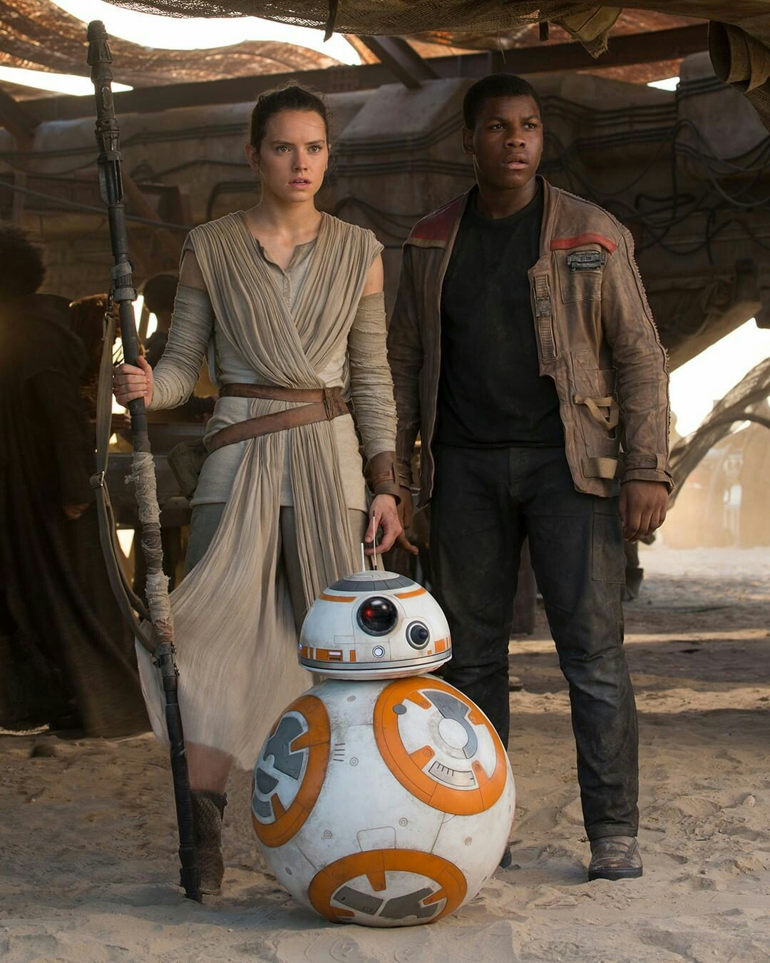 Imagem de Rey, Finn e BB8. Rey e Finn estão lado a lado e a imagem captura eles de corpo inteiro. Rey usa seu figurino original, com os braços enrolados numa faixa, um pano que cobre seus ombros e vai até o joelho. Por baixo, ela usa uma camiseta e uma calça, todos em tons de cinza. Ela usa uma bota e cinto marrom e segura sua arma. Finn, ao lado direito de Rey, usa uma blusa, calça e sapatos pretos e uma jaqueta marrom. Ele está desarmado mas sua postura é alerta, e assim como Rey, Finn olha para a frente assustado. Na frente dos dois, ao meio, está BB8, o droid redondo que é colorido em branco, com detalhes laranjas e cinzas.
