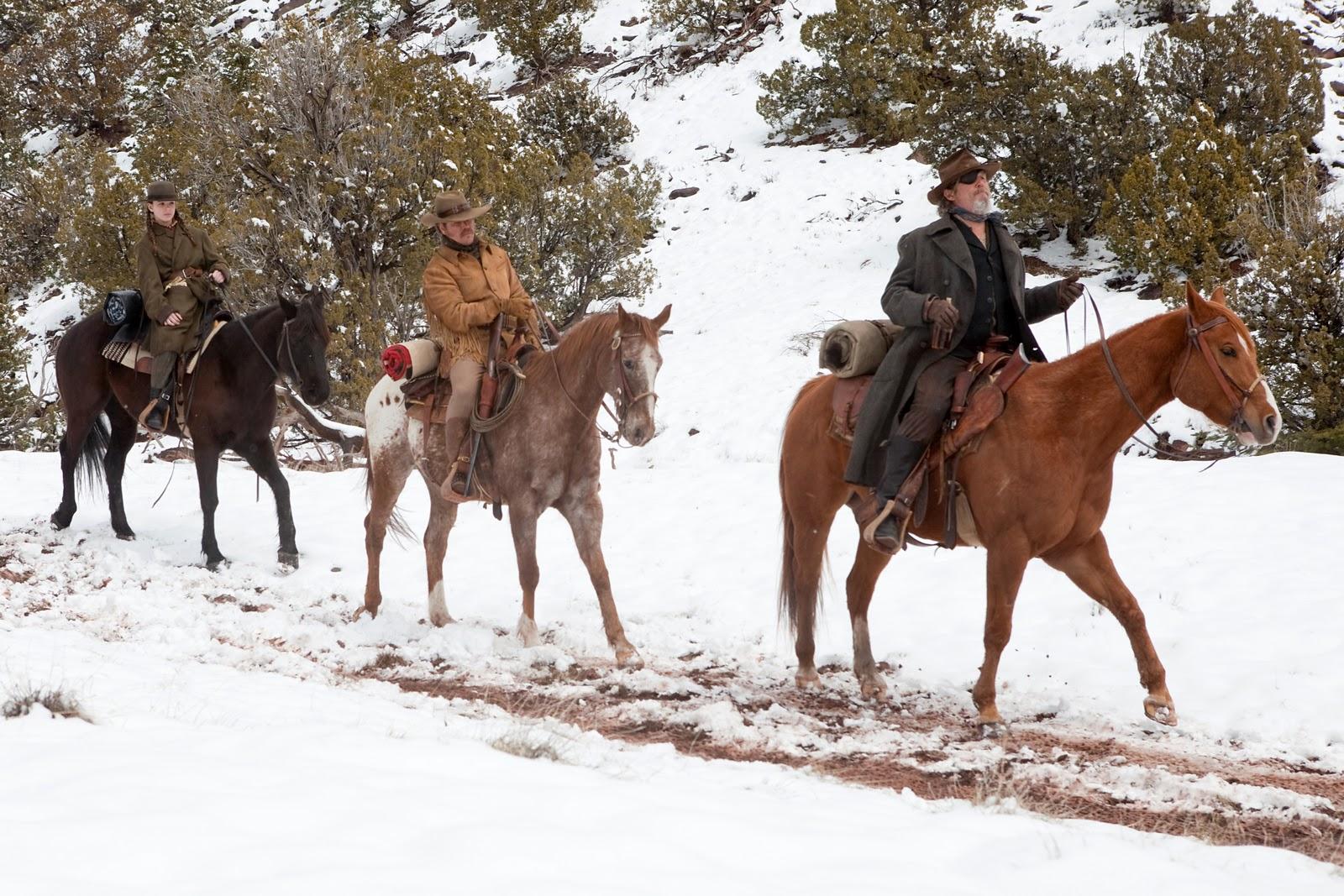 Trecho do filme Bravura Indômita. Na imagem, três pessoas estão montadas em três cavalos, que cavalgam na neve. No primeiro cavalo da frente, um homem usa um tapa-olho. No cavalo do meio, um homem veste roupa de cowboy normal. No último cavalo quem está em cima é uma garotinha.