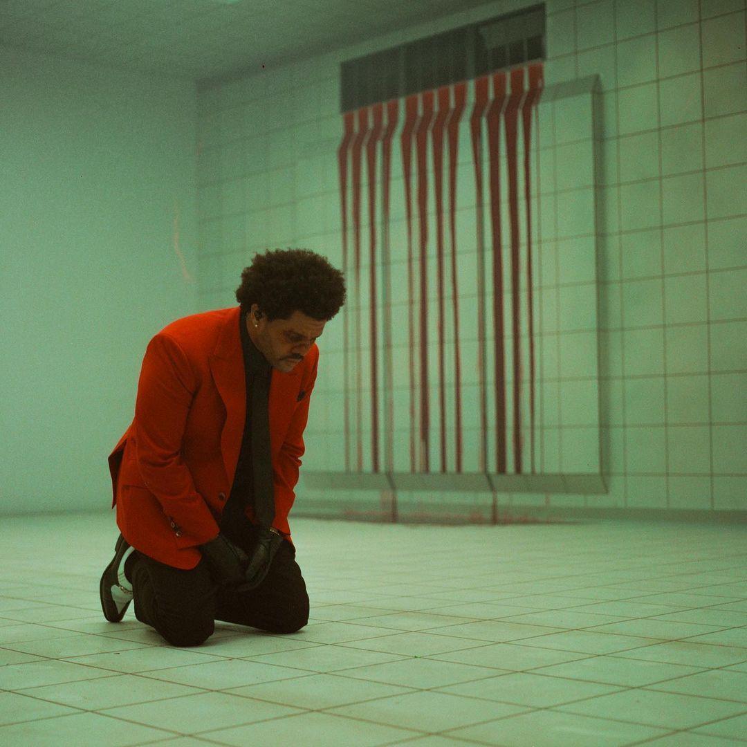 The Weeknd está ajoelhado num ambiente todo branco e com sangue escorrendo da ventilação. Ele é um homem negro de 30 anos, com cabelo estilo blackpower, usa um terno vermelho com camisa preta, luvas pretas e tênis preto com detalhes brancos na ponta