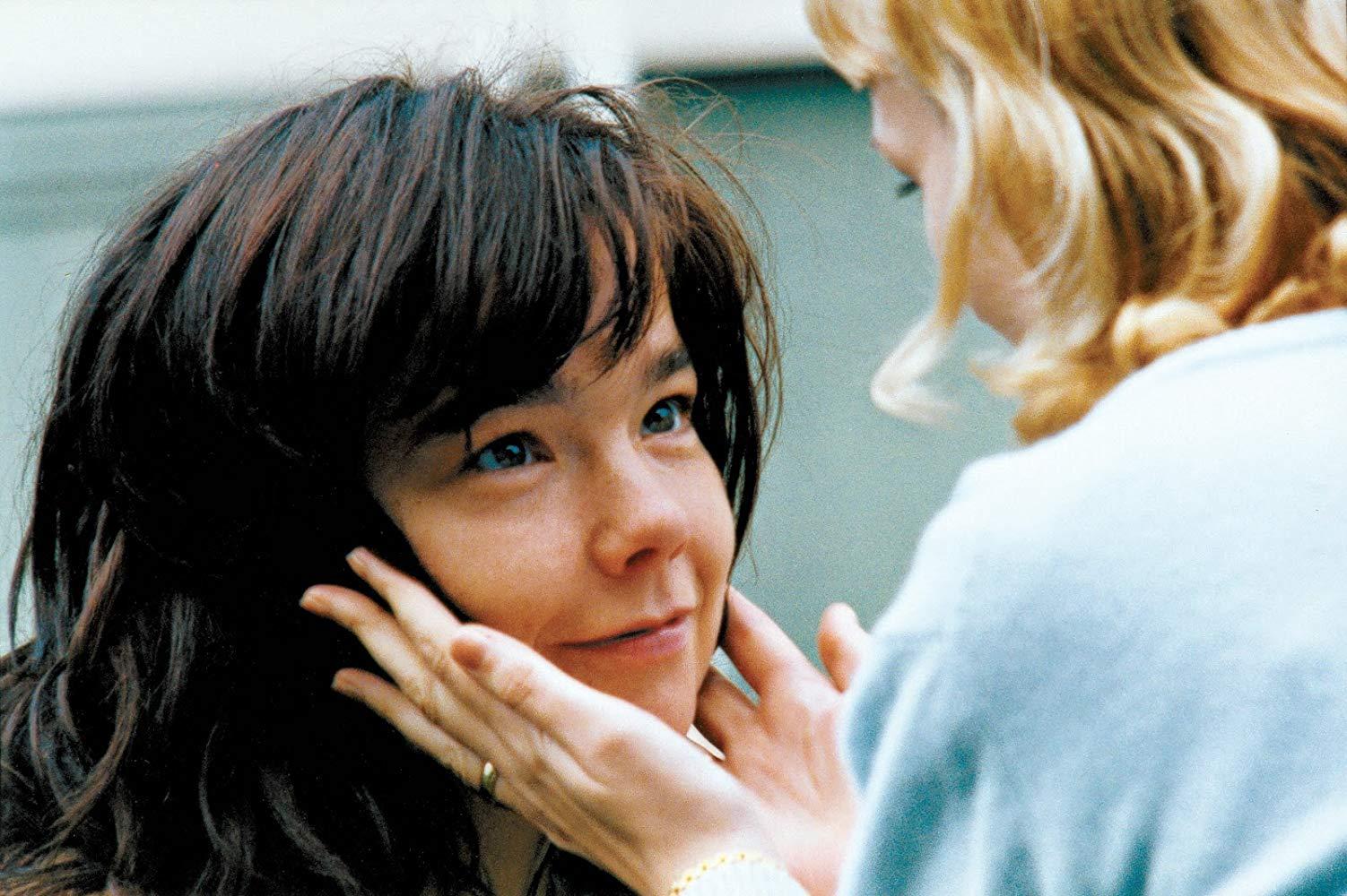 Cena do filme Dançando no Escuro. A imagem mostra uma mulher loira com as mãos no rosto de Björk, que olha para seu rosto e sorri.
