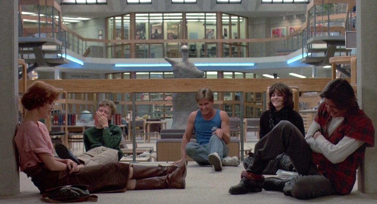 A imagem é de uma das cenas do filme, em que os personagens estão sentados no chão da biblioteca, em um semi-círculo. Claire e John estão encostados em uma pilastra, um de frente para o outro. Enquanto Brian, Andrew e Allison estão do outro lado da roda. Todos estão rindo.