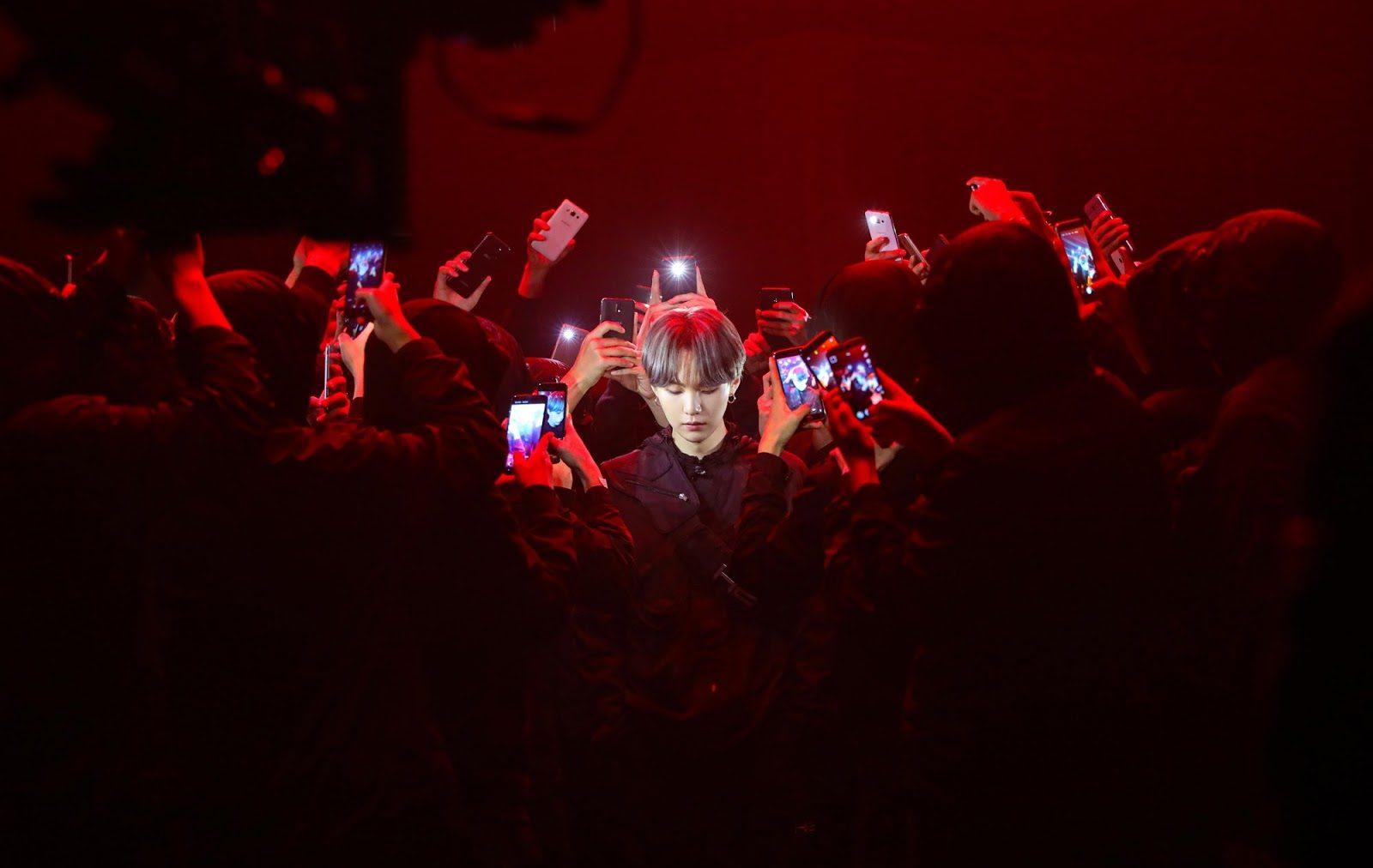 Foto de Suga em uma performance do BTS. Ele está ao centro da imagem, cercado por pessoas que o fotografam com os flashes de seus celulares. Ele olha para baixo é visível somente do ombro para cima. Seu cabelo é castanho médio, na altura das orelhas, e está dividido ao meio. Ele também usa um brinco de argola na orelha esquerda e suas roupas são pretas. Toda a composição da imagem tem tons avermelhados, incluindo o fundo.
