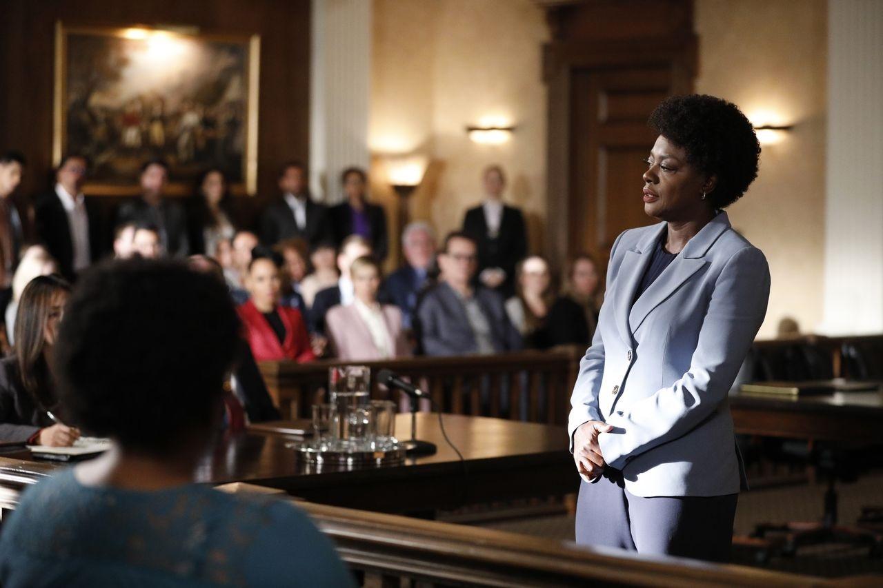 A imagem é de uma das cenas da sexta temporada de How To Get Away With Murder. Nela, vemos a personagem Annalise Keating em um tribunal, falando em direção ao júri. Annalise é uma mulher negra, de cabelos crespos curtos, ela veste um terno cinza claro e uma calça cinza escura.