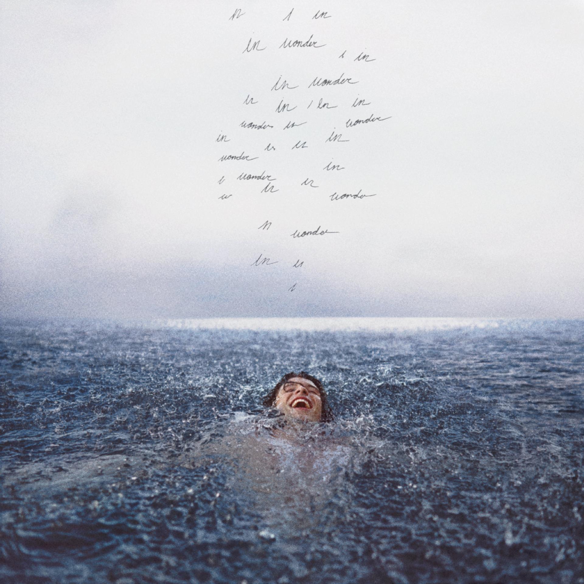 Capa do disco Wonder. Shawn Mendes está nadando e sorrindo, acima dele vemos escritos ilegíveis
