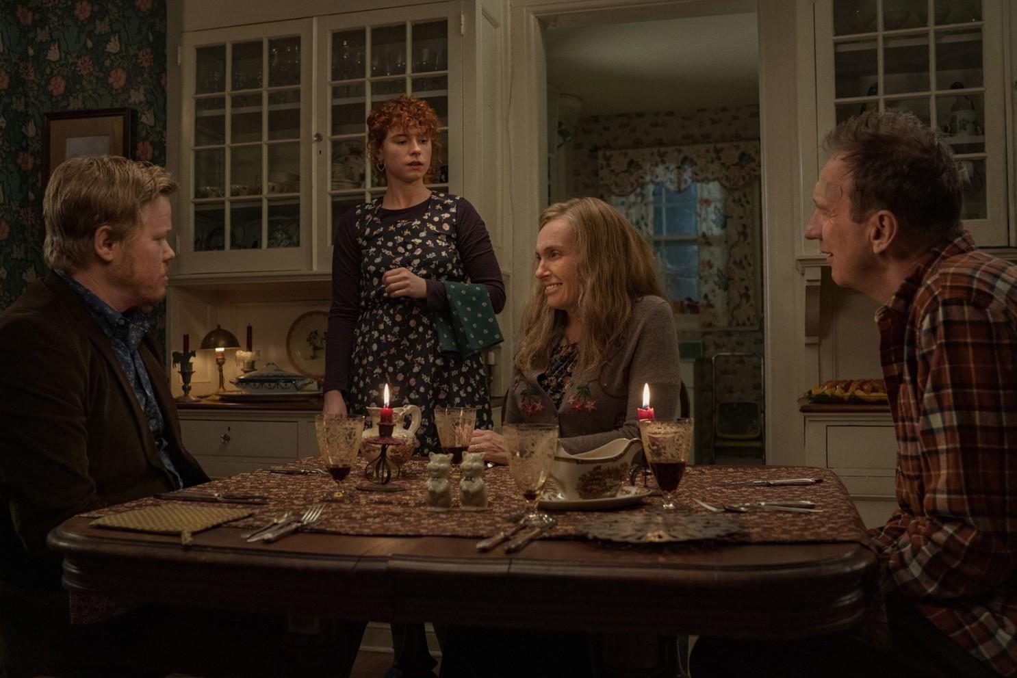 Três adultos estão sentados à mesa, enquanto a jovem mulher está de pé. O ambiente é mal iluminado e tem tons terrosos