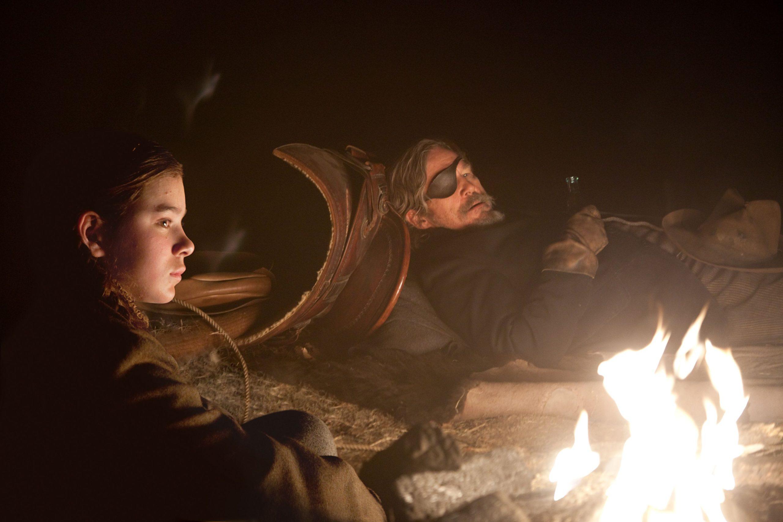 A imagem mostra uma garotinha e um homem usando tapa-olho em volta de uma fogueira. Eles estão olhando ambos para a frente. O homem está deitado. É noite.