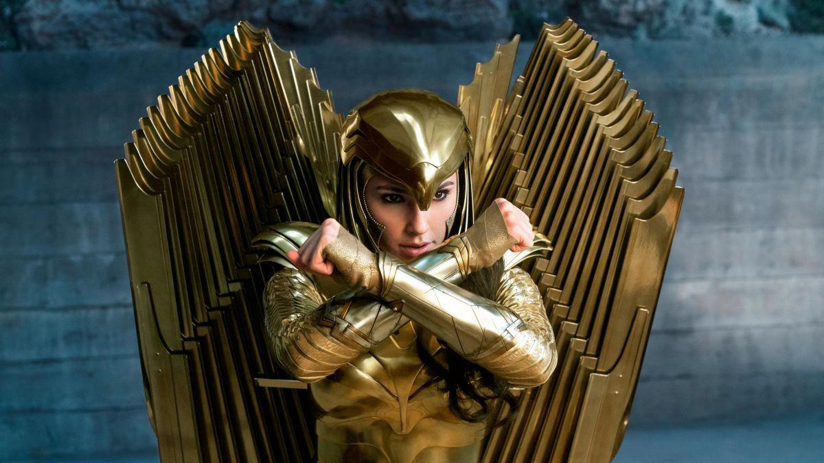 A imagem mostra a Mulher Maravilha usando sua armadura dourada que remete a uma águia. Ela tem os braços cruzados na altura do rosto em forma de X.