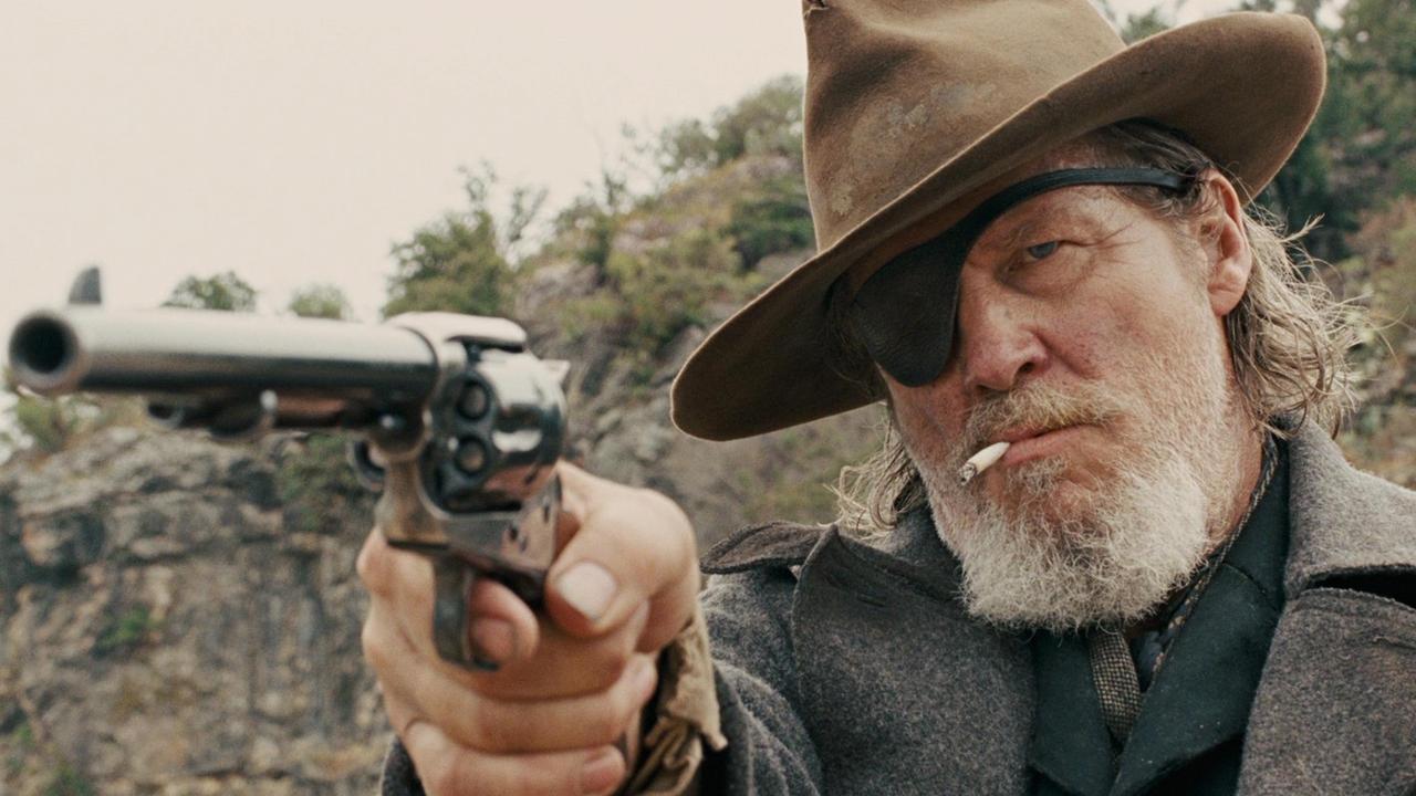 A imagem mostra um homem de tapa-olho e chapéu. Ele fuma um cigarro e aponta uma arma em direção à esquerda da imagem. Ele está num ambiente de deserto, e possui barba. Tem aparência de velho.