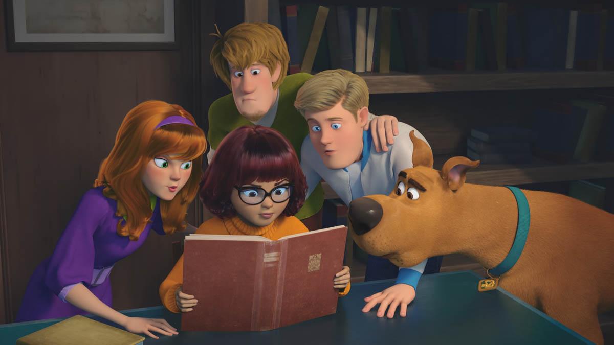 A imagem mostra toda a turma da Mistério S/A. Da esquerda para a direita estão: Daphine com um vestido roxo, cabelos ruivos soltos e tiara também roxa; Velma mo uma cacharrel laranja, cabelos curtos castanhos, óculos de grau e um livro nas mãos; Salsicha com uma blusa verde e cabelos caramelo despenteados, Fred com uma jaqueta branca de gola azul e cabelos loiros penteados para trás e Scooby com sua coleira azul e pelos marrons.