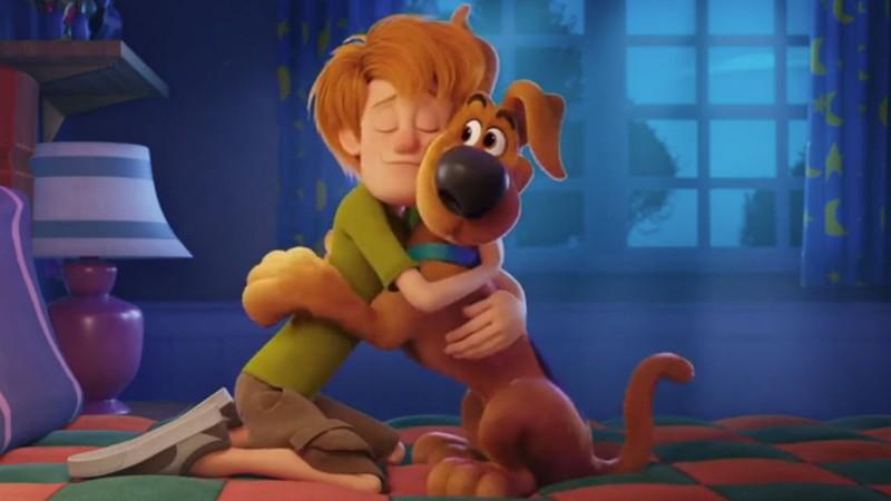 A imagem mostra Salsicha e Scooby abraçados em cima de uma cama. Eles usam seus figurinos clássicos, sendo o de salsicha a blusa verde, bermuda cáqui e tênis e de Scooby a coleira azul.