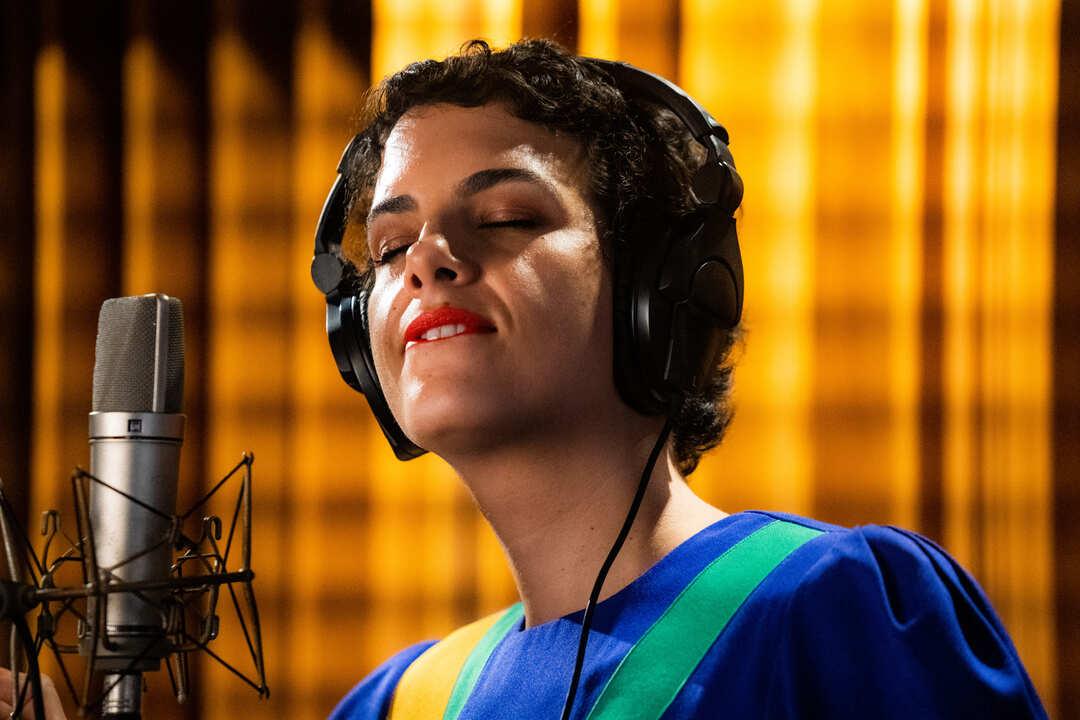 Há um fundo amarelo. No primeiro plano, está Céu, uma mulher branca, de cabelos curtos e escuros. Está vestindo uma blusa azul, com uma listra verde e uma amarela. Tem um headphone nos ouvidos e a sua frente está um microfone de gravação profissional. Ela está com os olhos fechados e mordendo os lábios.