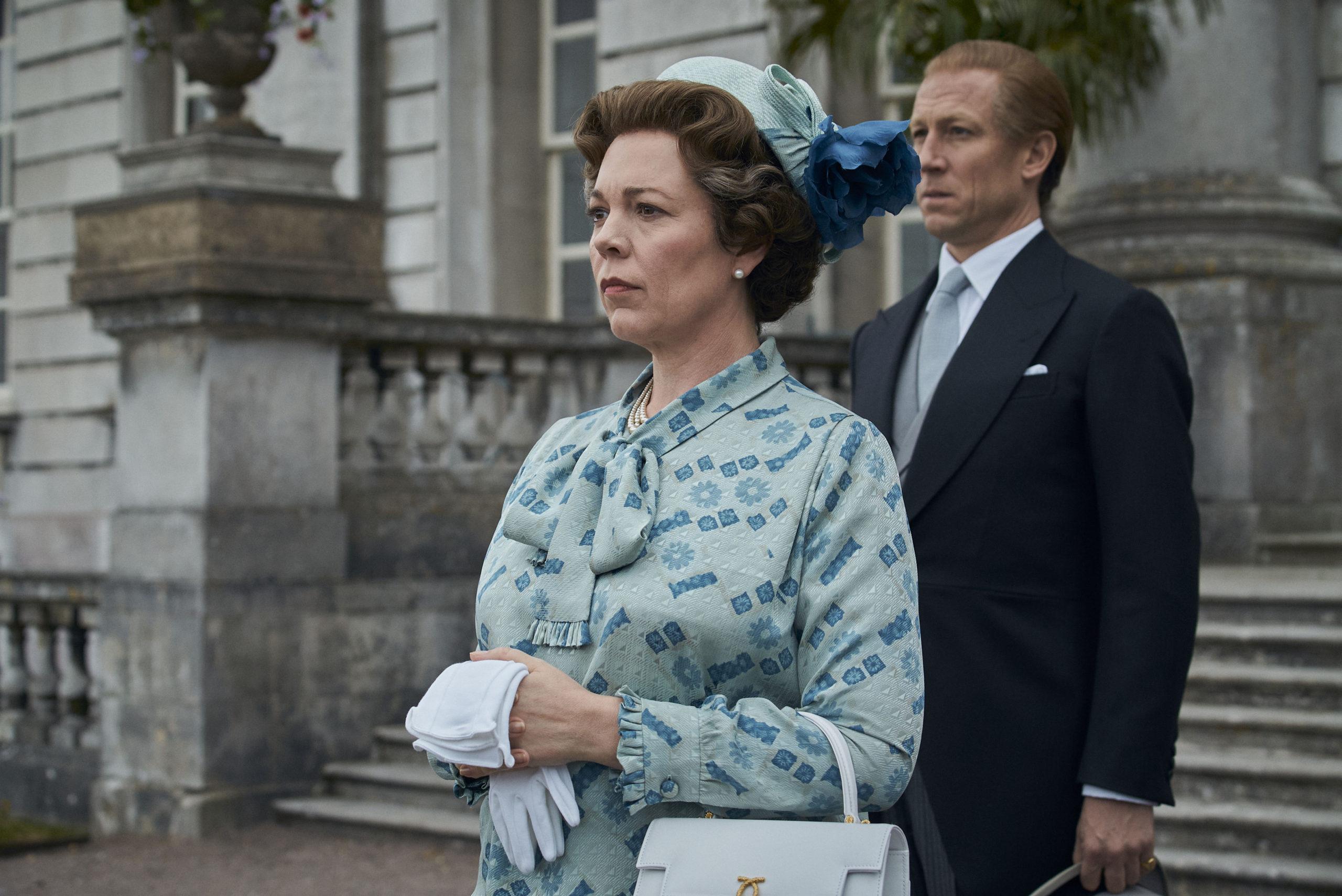 Na imagem, Rainha Elizabeth no centro e seu marido, Príncipe Philip logo atrás. A Rainha veste um vestido verde claro estampado e um chápeu verde, equanto o Princípe veste um terno preto.,