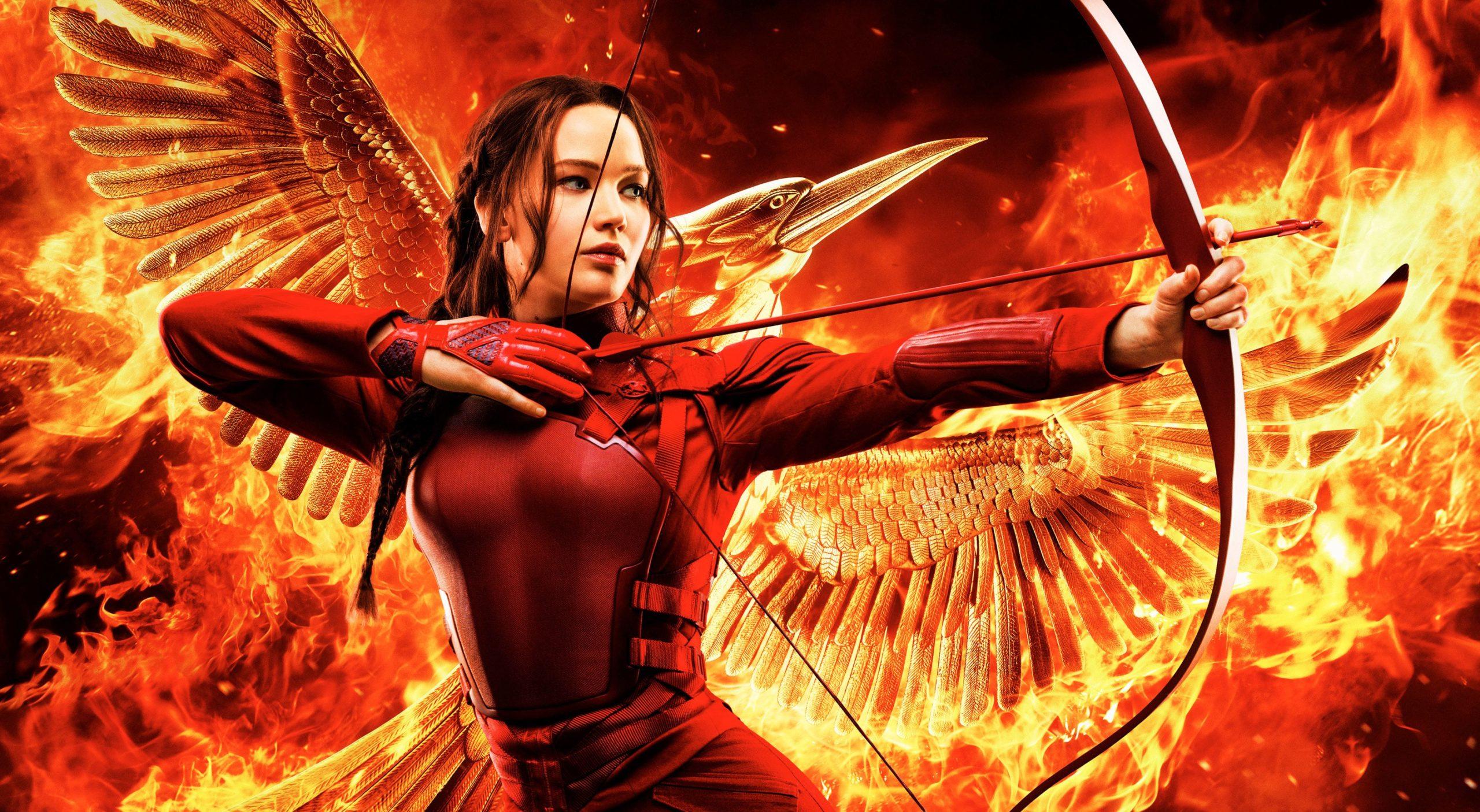 A imagem mostra Katniss com um macacão vermelho. Ela está segurando um arco e flecha pronto para ser disparado e seu cabelo, castanho escuro, está penteado em uma trança lateral. Ao fundo vemos uma ave, o tordo, em chamas.