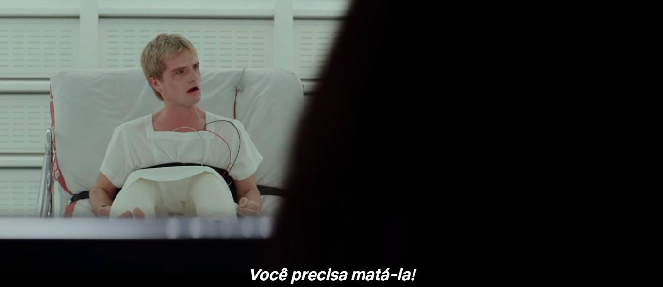A imagem mostra Peet em uma maca. Ele tem o corpo amarrado a cama e usa uma roupa hospitalar branca. Seu rosto demonstra desespero e raiva.