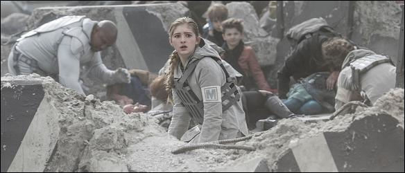 A imagem mostra Prim em meio aos destroços como uma trança loira lateral. Ela usa uma roupa militar cinza e ao fundo vemos pessoas machucadas.