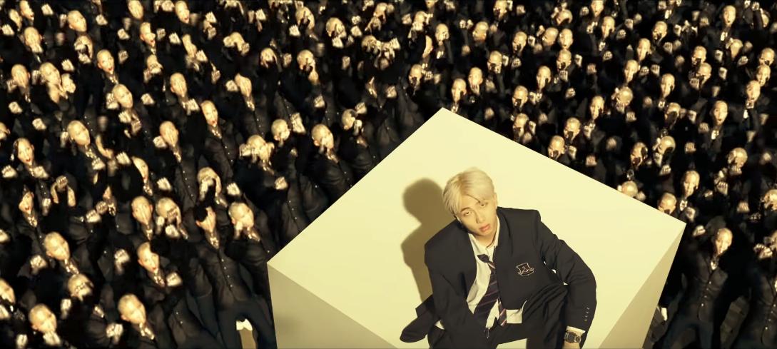 """Imagem de RM no videoclipe da música """"Persona"""". A visão que temos dele é de cima, ele está sentado em um cubo branco no lado direito da imagem, usando um terno preto que parece ser um uniforme escolar. Abaixo dele e preenchendo todo o resto da imagem, várias figuras humanas sem rosto estão o observando e gritando."""