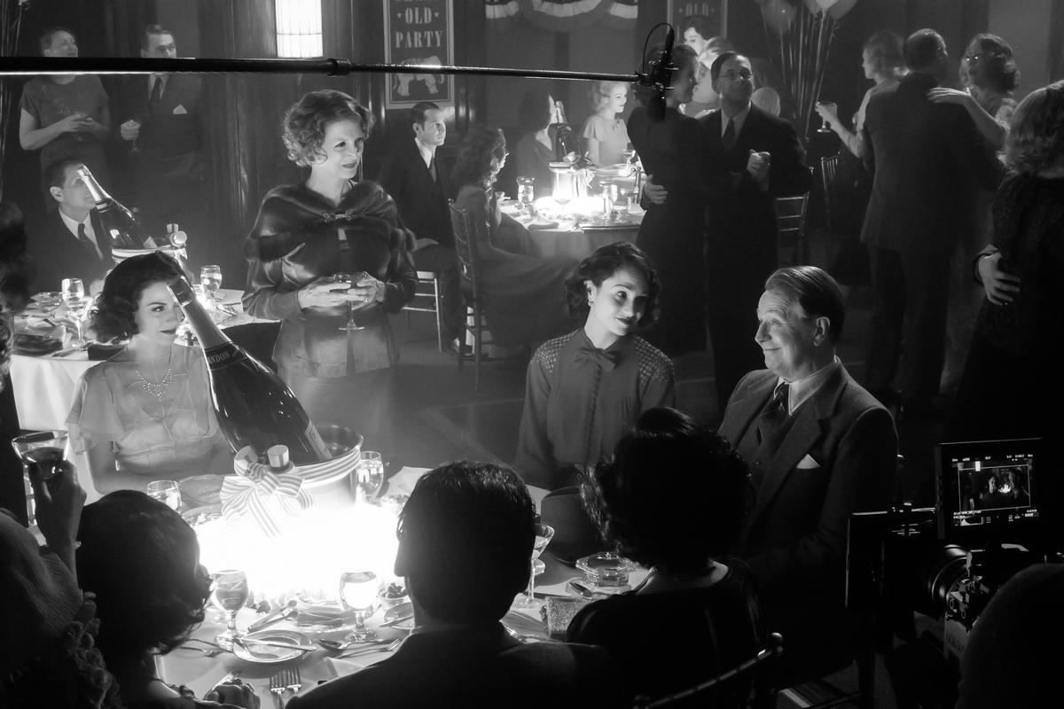 A imagem está em preto e branco. Vemos uma mesa com um balde com champagne dentro. Ao redor dela, três mulheres olham para a figura de Gary Oldman, que sorri. De fundo, temos outras mesas e casais dançando. Ao redor, vemos um microfone e uma câmera de filmagem, indicando os bastidores.