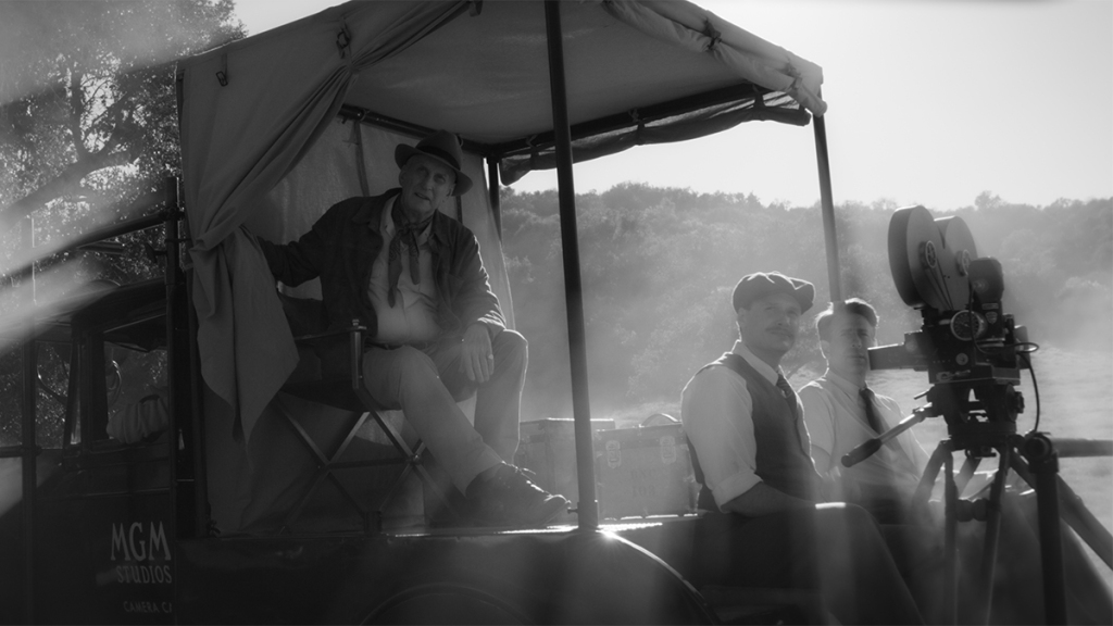 A imagem está em preto e branco. Charles Dance senta na parte de trás de um veículo do estúdio MGM. À frente, dois homens o acompanham, junto com uma grande câmera de filmagem.