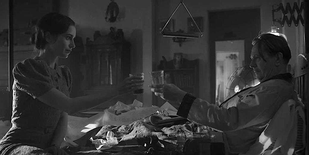 A imagem está em preto e branco. Lily Collins, à esquerda, está sentada em cima de uma cama. Ela veste um vestido simples com mangas. À direita, Gary Oldman está deitado na cama usando pijamas de mangas compridas. A cama está cheia de papéis e de fundo há o ambiente de um quarto, com uma porta para um corredor. Collins e Oldman brindam, cada um com um copo em mãos.